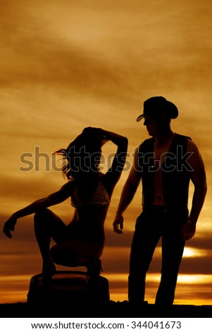 a silhouette of a woman on her barrel with the cowboy standing next to her. - stock photo