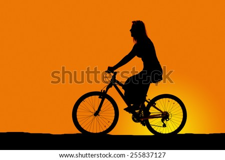 A silhouette of a woman on her bike, riding in the outdoors. - stock photo