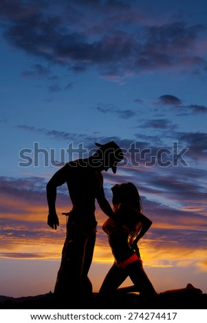 A silhouette of a woman on her knees looking into her cowboys face. - stock photo