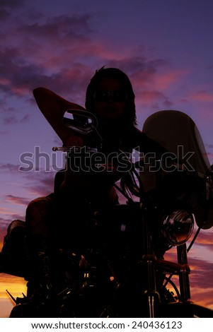 a silhouette of a woman on her motorcycle. - stock photo