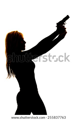 A silhouette of a woman pointing her gun into the sky. - stock photo