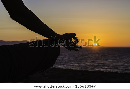 A silhouette of a woman practicing yoga in the lotus position in a sunset/ Woman in lotus position - stock photo