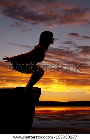 A silhouette of a woman preparing to jump into the water - stock photo