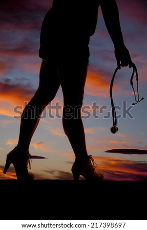 A silhouette of a woman's legs holding a stethoscope in her hands. - stock photo