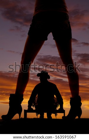 A silhouette of a woman's legs with a cowboy sitting on a fence. - stock photo