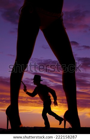 a silhouette of a woman's legs with a cowboy with a pistol in between them. - stock photo