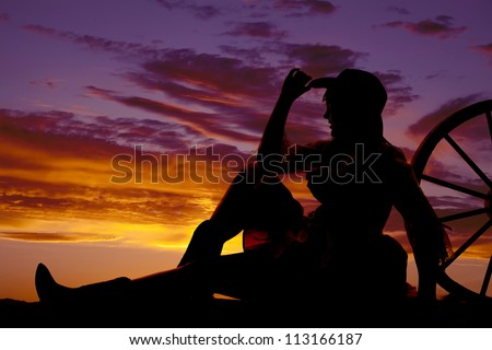 a silhouette of a woman sitting and leaning back against a wagon wheel with a beautiful sunset. - stock photo
