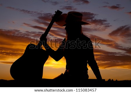 A silhouette of a woman sitting down and holding on to her guitar. - stock photo