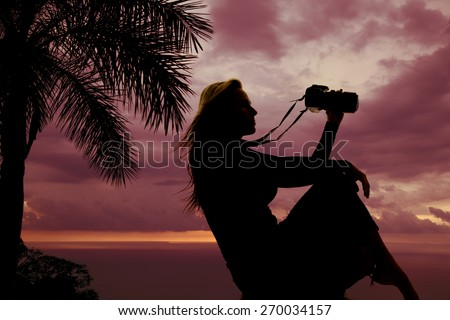 a silhouette of a woman sitting holding on to her camera. - stock photo
