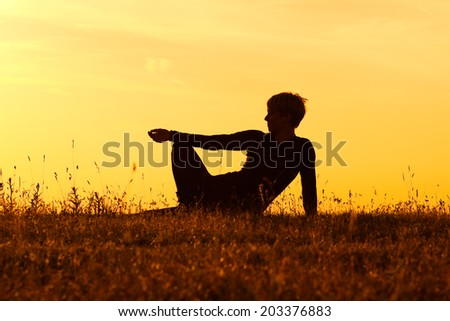 A silhouette of a woman sitting in the nature and enjoy watching the sunset,Enjoying the sunset - stock photo