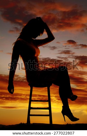 A silhouette of a woman sitting on a stool, with her head down in sadness. - stock photo