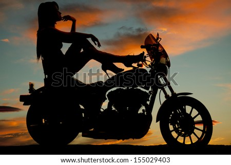 A silhouette of a woman sitting on her bike relaxing and looking out to the sky - stock photo