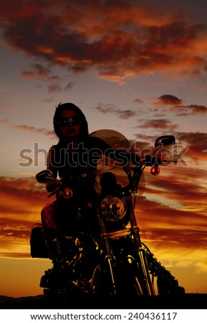 A silhouette of a woman sitting on her motorcycle with her glasses on. - stock photo