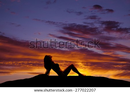 A silhouette of a woman sitting with the sun glow on her skin. - stock photo
