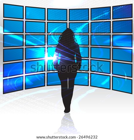 A silhouette of a woman standing in front of a wall of tv screens. - stock photo