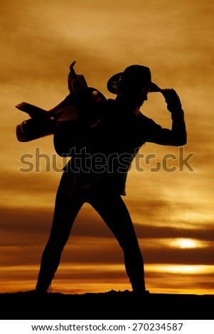 a silhouette of a woman touching the brim of her hat holding on to her saddle. - stock photo