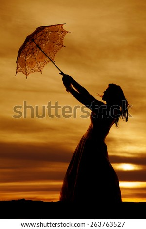 A silhouette of a woman trying to hang on to her umbrella in the wind. - stock photo