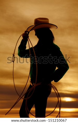 A silhouette of a woman with a rope and cowgirl hat, with a beautiful sunset in the background. - stock photo