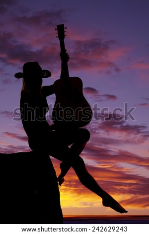A silhouette of a woman with her guitar on her lap on a cliff. - stock photo