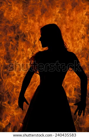 A silhouette of a woman with her hands out in her dress. - stock photo