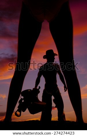 A silhouette of a woman with her legs wide, and her cowboy showing through them. - stock photo