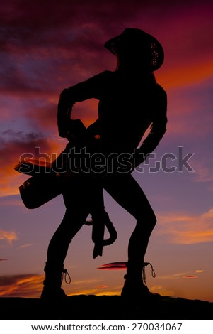 A silhouette of a woman with her saddle on her hip. - stock photo