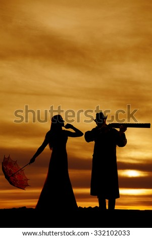 a silhouette of a woman with her umbrella looking to her cowboy who is pointing his rifle. - stock photo