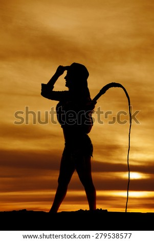 A silhouette of a woman with her western hat on and a whip. - stock photo