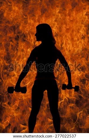 A silhouette of a woman with weights, with a fire background. - stock photo