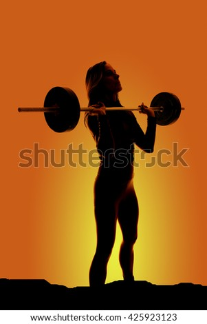 A silhouette of a woman working out with a barbell on her chest. - stock photo