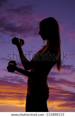 a silhouette of a woman working out with weights with a colorful sky in the background. - stock photo