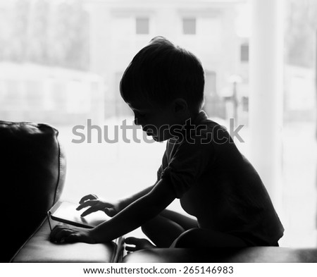 A silhouette of a young boy on a tablet or computer.   Symbolising the dangers of the internet.  - stock photo