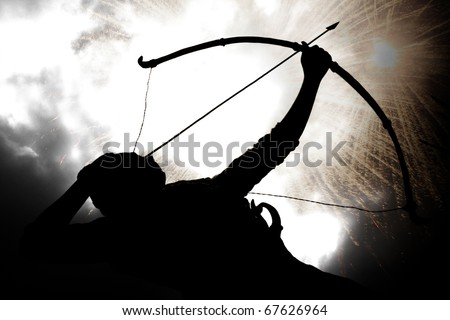 A silhouette of an archer, on the backdrop of a sky with exploding gun powder. - stock photo