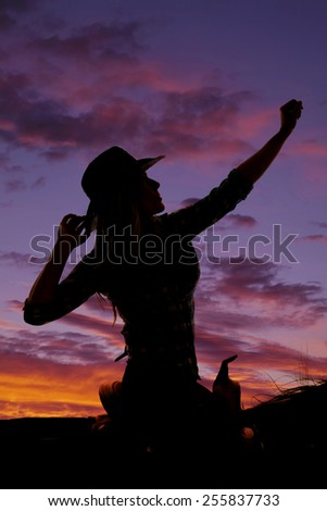 A silhouette of cowgirl sitting on her horse with her hand up in the air. - stock photo