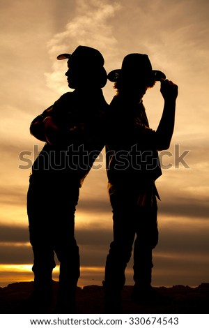 a silhouette of two cowboys in the outdoors, one is touching the brim of his hat. - stock photo