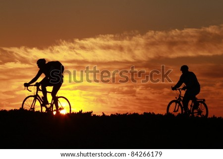 a silhouette of two people riding there bikes on a trail  in the early morning sun rise - stock photo