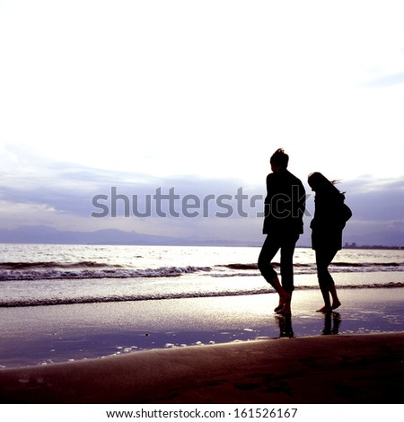 A silhouette of two people walking on a beach. - stock photo
