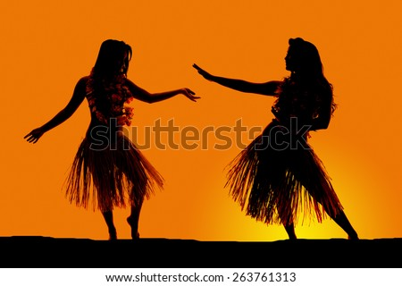 A silhouette of two women dancing in their grass skirts, in the outdoors. - stock photo