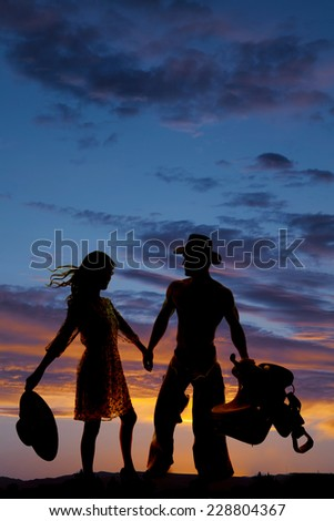 A silhouette of woman holding on to her cowboys hand. - stock photo