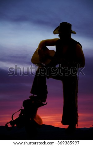 A silhouette on a saddle with his foot up playing his guitar. - stock photo