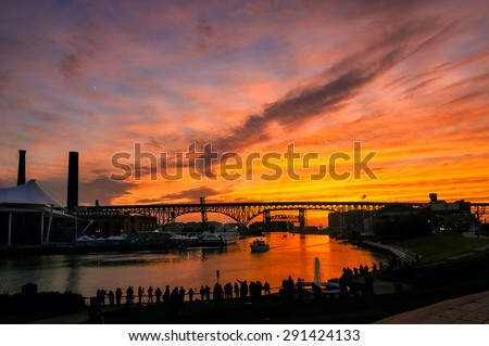 A silhouetted crowd of photographers lines the east bank of the Cuyahoga River in Cleveland to shoot the summer solstice sunset - stock photo