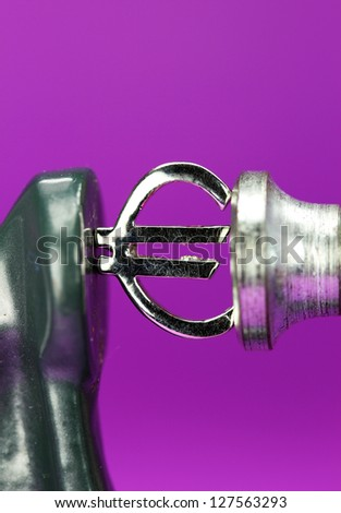 A silver Euro symbol placed in a clamp with a purple background, indicating the pressure is on the currency. - stock photo