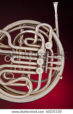 A silver French horn isolated against a spotlight red background in vertical format. - stock photo