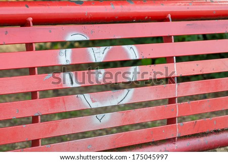 A silver graffiti heart on a red bench - stock photo