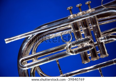A silver marching French horn isolated on a blue background in the horizontal format. - stock photo