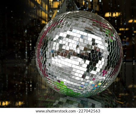 A silver mirror ball lies on a reflective glass surface in a darkened room. - stock photo
