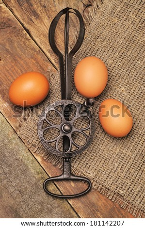 A silver vintage mixer and three raw eggs - stock photo