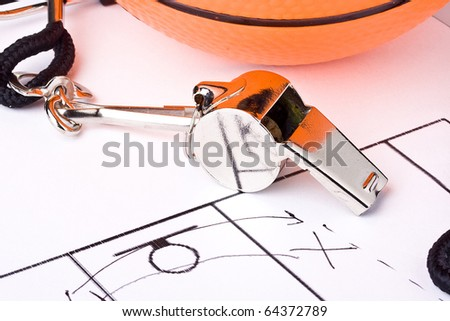 A silver whistle laying next to an orange basketball and the game plan. - stock photo