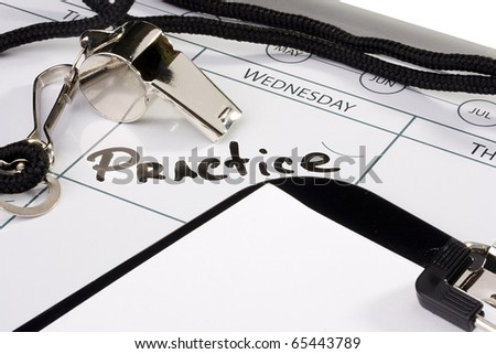 A silver whistle laying on a calendar next to a clipboard. - stock photo