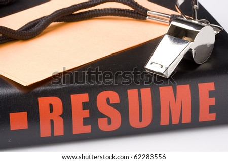 A silver whistle laying on a very long resume of an experienced coach. - stock photo